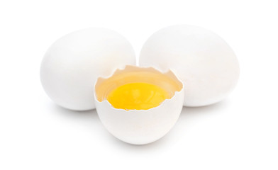 One broken egg with two whole eggs on white background.