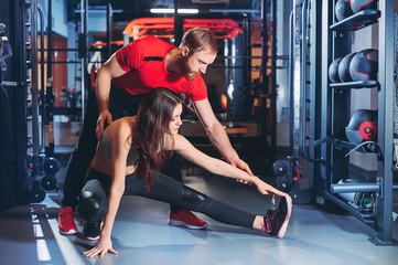 Personal trainer helps the girl to do exercises in the gym