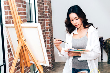 Young woman artist drawing on canvas with color palette and watercolor paints at home