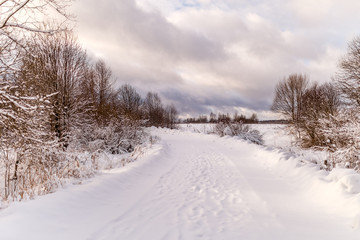 Photo of snowy landscape with cloudy sky and road
