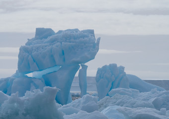 Close Up of an Antarctic Sound Iceberg with blue color and ice stacked in haphazard fashion.