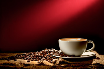 Cup of coffee latte and coffee beans on reddish brown background