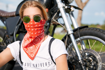 Beautiful serious female biker with covered face wears trendy sunglasses, sits against motorbike, rests in open air after speed route far from urban territory. Skilled driver enjoys motorbike drive
