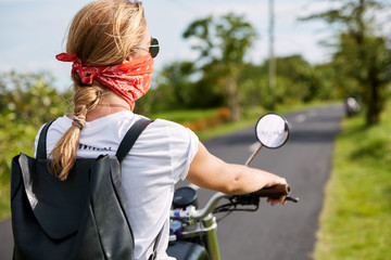 Back view of active female biker wears bandana on face, rides motorbike on asphalt, carries something in black bag, feels freedom as spends free time in countryside. People and lifestyle concept