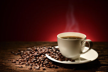Cup of coffee with smoke and coffee beans on reddish brown background
