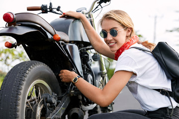 Cheerful female biker or motorist tries to solve problem with transport, repairs motorbike during trip. Talented woman driver fixes some parts of motorcycle alone. Repairing transport on way