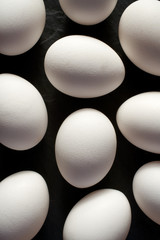 Chicken eggs with white shells on a black background, top view, close-up