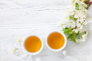 Two cups of tea and branch of blossom cherry on white wooden table.