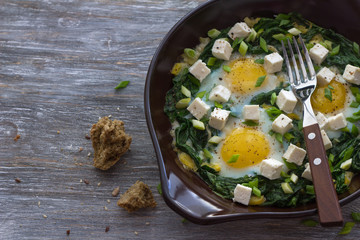 Green shakshuka with spinach, leek and feta in a ceramic frying pan on a wooden table with bread, free space, selective focus. Delicious healthy home food