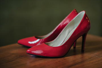 red high-heeled shoes close-up on the table for the bride
