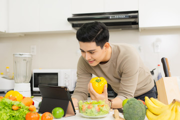 Asian handsome man looking recipe on digital tablet in kitchen at home
