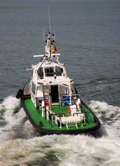 Tugboat sailing in the sea. Tugboat making maneuvers.