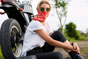 Shot of carefree stylish female in sunglasses and bandana, poses near motorbike, sits on road, enjoys high speed and nature view. Pretty fashionable woman has adventure or journey alone outside