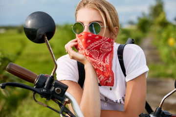 Beautiful hipster female has motorcycling tour on fast motorbike, rests for minute, has pensive expression, wears shades and bandana, has active rest during summer resort. Extreme sport outdoor