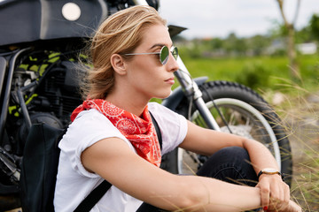 Serious blonde woman in casual clothing and sunglasses sits near her favourite motorbike, breathes fresh air, likes exteme outdoor activities. People, journey, lifestyle and freedom concept.