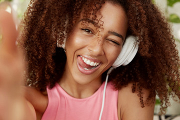 Close up shot of cheerful African American female listens pleasant music with headphones, poses for selfie, being in good mood. Teenage dark skinned girl enteratins herself with modern device