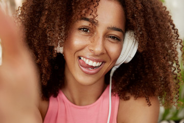 Headshot of positive dark skinned mixed race female model listens favourite track in headphones, makes selfie with unrecognizable modern device, demonstrates shining smile. Entertainment and people