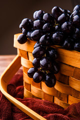 Photo of black grapes in wooden basket with claret cloth