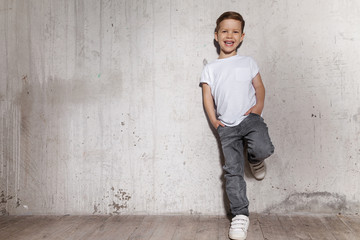 Little fashionable boy posing in front of gray concrete wall. Portrait of smiling child in white T-shirt and gray trousers. Concept of style and fashion for children. Wall mural