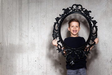 Cute little boy holds black decorative frame. Portrait of smiling male child in black T-shirt. Positive little guy, gray wall on background, copy space.