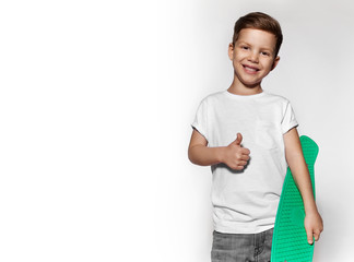 Cute little boy with skateboard showing gesture thumb up. Concept of sport and positive. Portrait of skater boy, photo isolated on white background. Little guy in white T-shirt with green skateboard.