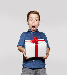 Happy little boy with a gift, white box with red ribbon. Photo isolated on gray background. Smiling boy holds present box and very surprised. Concept of holidays and birthday.
