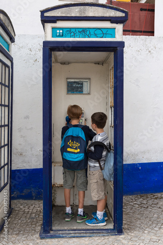 Children Making Phone Call inside Vintage Blue Phone Call Box in
