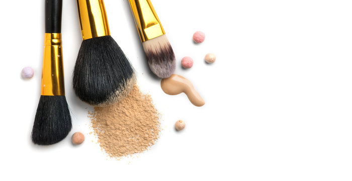 Cosmetic liquid foundation or cream, loose face powder, various brushes for apply makeup. Make up concealer smear and powder isolated on a white background. Products for professional face skin makeup