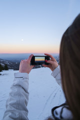 Girl in jacket photographing winter landscape