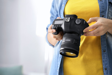 Female photographer holding camera indoors
