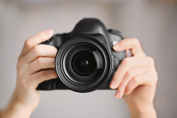 Female photographer holding camera on blurred background