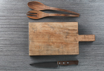 Cutting board and kitchen utensils on wooden background. Cooking master classes