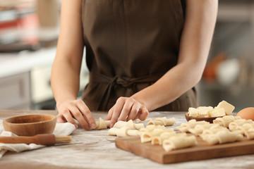 Woman preparing croissants in kitchen