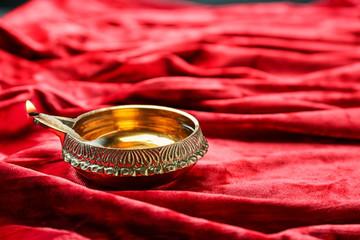 Diwali diya or clay lamp on red fabric