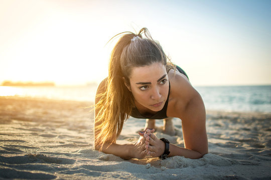 Beautiful sporty woman in plank position on the beach.