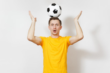 Inspired young fun European man, fan or player in yellow uniform hold on head soccer ball, cheer favorite football team isolated on white background. Sport, play football, healthy lifestyle concept.
