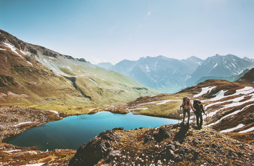 Couple backpackers hiking in mountains over lake Traveling together Lifestyle wanderlust concept adventure vacations outdoor aerial view.