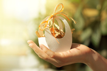 delivery Easter gift/ egg in a festive package adorned with bow in hand