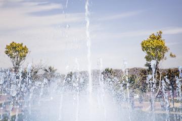 Salpicaduras de agua de la fuente en un día soleado bajo un cielo azul