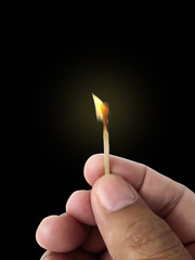 Male hands hold a match with a flame. The background is dark