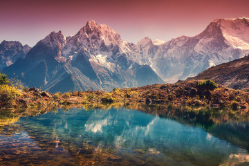 Poster Reflection Beautiful landscape with high mountains with snow covered peaks, red sky reflected in lake. Mountain valley with reflection in water in sunset. Nepal. Amazing scene with Himalayan mountains. Nature