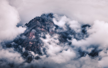 Wall Mural - Mountains in clouds in overcast evening in Nepal. Landscape with beautiful high rocks and dramatic cloudy sky at sunset. Nature background. Fairy scene. Amazing mountains at dusk. Vintage style
