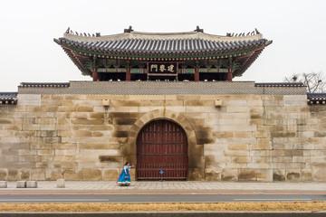 Korean woman walking in front of Geonchunmun Gate of Gyeongbokgung Palace. It is landmark in Seoul, South Korea, Asia.