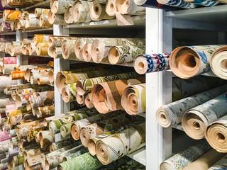 a lot of old, retro, vintage wallpaper rolls on shelves
