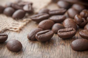 grains de café et toile de jutte sur table en bois