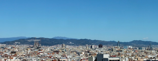 panorama of the city of barcelona showing the cathedral business district and housing with mountains in the distance