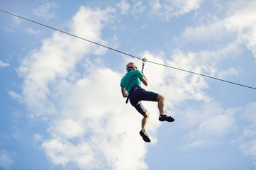 a man descends on a rope, a sport in an extreme park, A man walking along a zip line