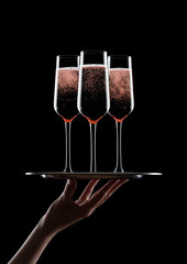 Hand holds tray with pink rose champagne glasses