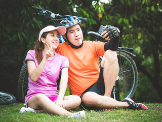 Asian man and woman  take a photo by smartphone after riding bicycle in outdoor park