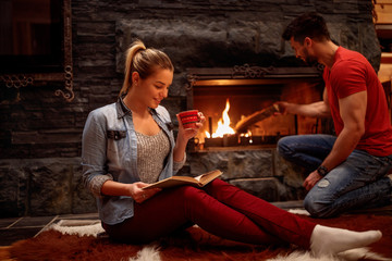 romantic couple relaxing at home front of fireplace